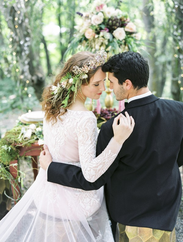 Bride and groom sitting at wedding table touching heads