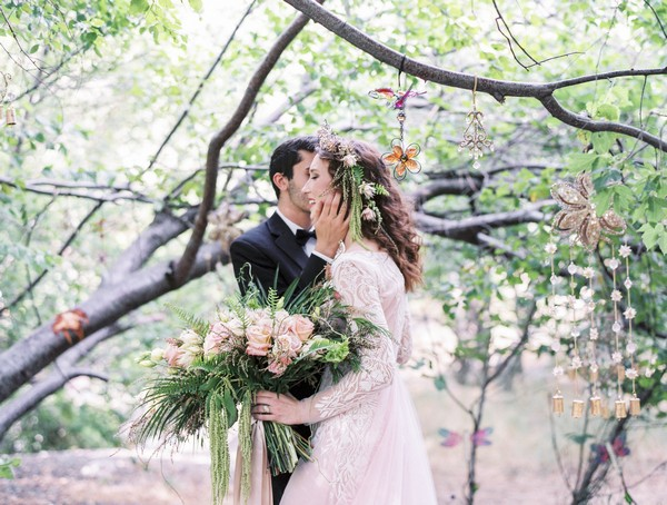 Groom kissing bride on the cheek under tree branches