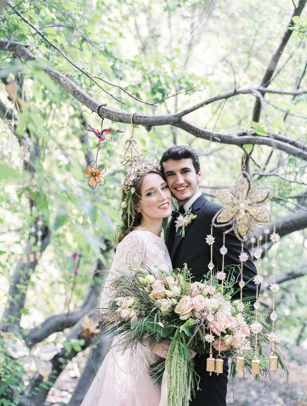 Bride and groom standing under tree branches in woods