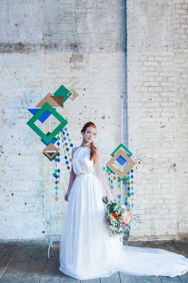 Bride standing in front of geometric wedding backdrop