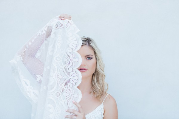 Bride holding lace across face
