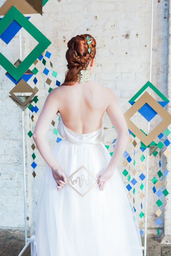 Bride holding geometric Mrs sign behind her back