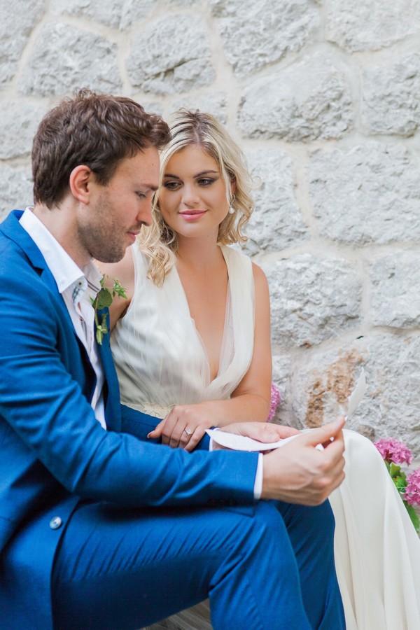 Bride listening as groom reads note