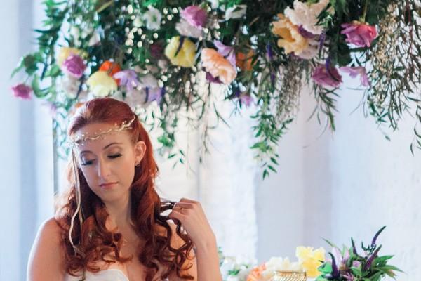 Bride sitting under hanging floral arrangement