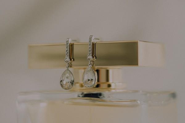 Earrings on top of perfume bottle