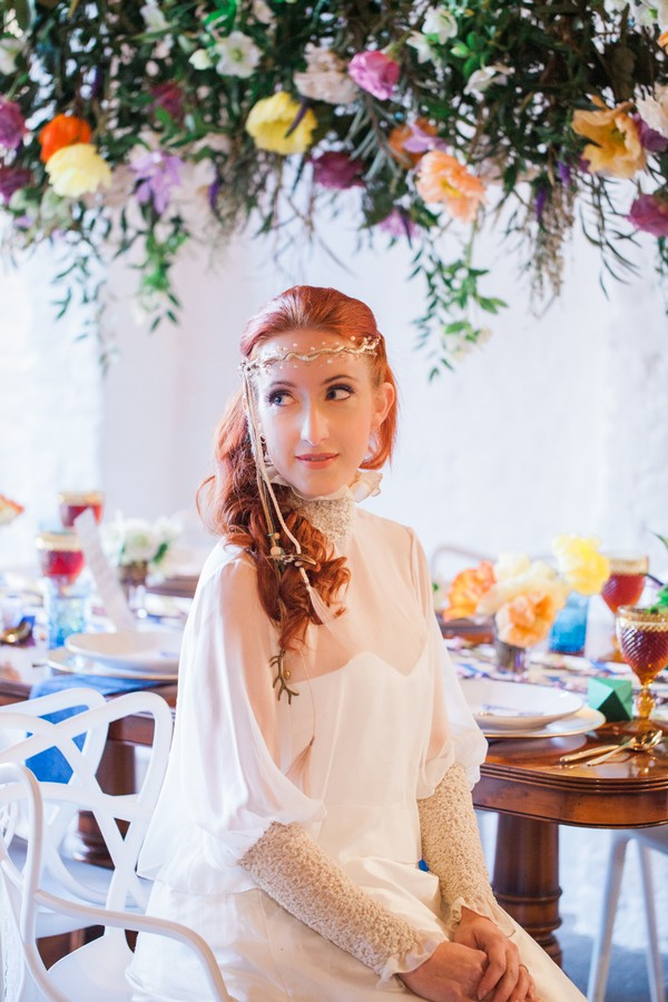 Bride wearing forehead chain sitting at wedding table