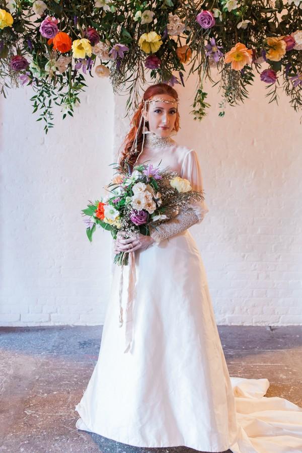 Bride holding bouquet under hanging floral arrangement