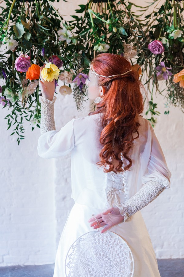 Bride looking at flower holding dreamcatcher behind her back