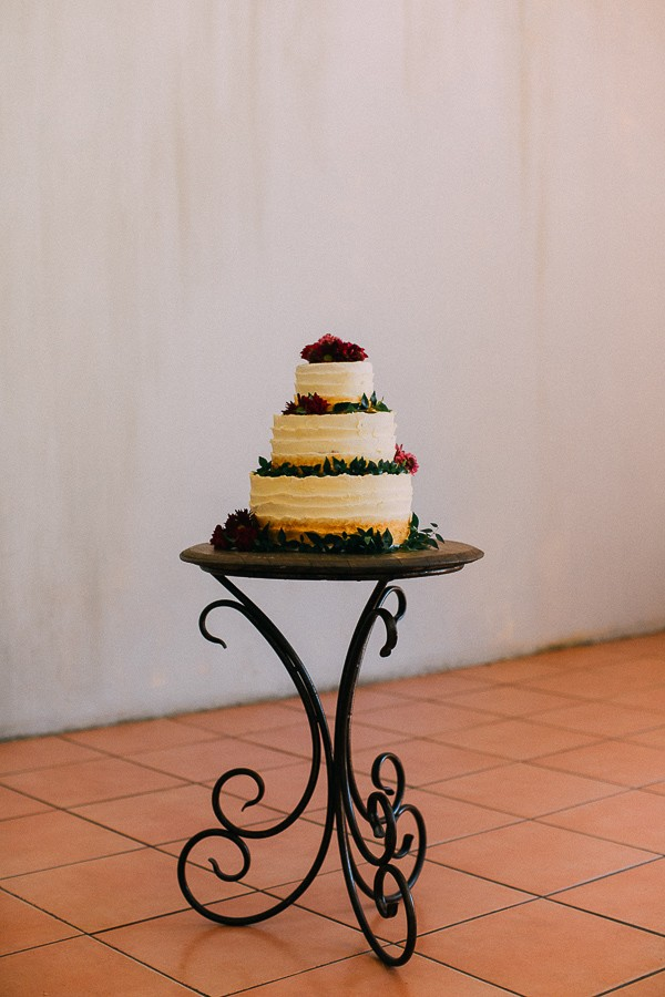 Cream wedding cake with foliage and berries