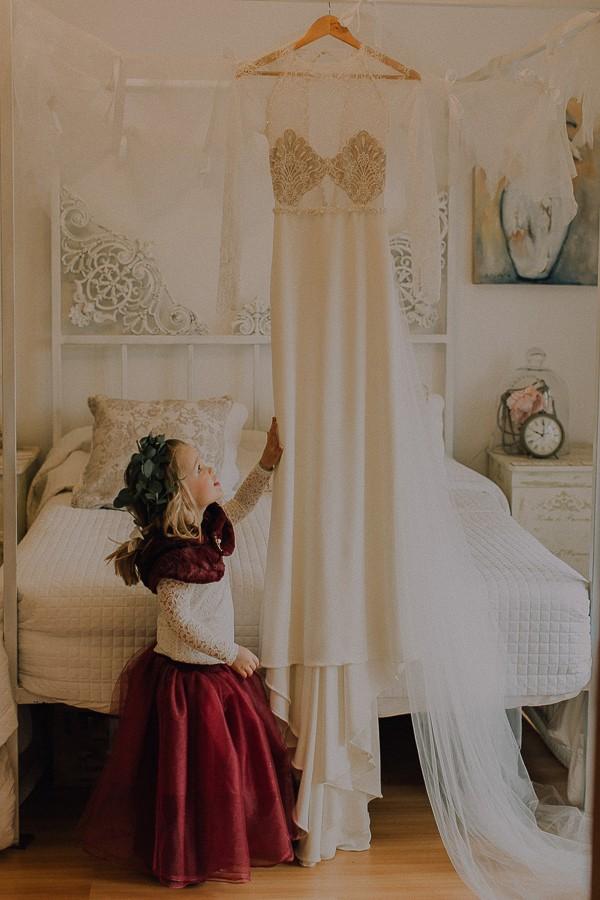 Flower girl looking at hanging wedding dress