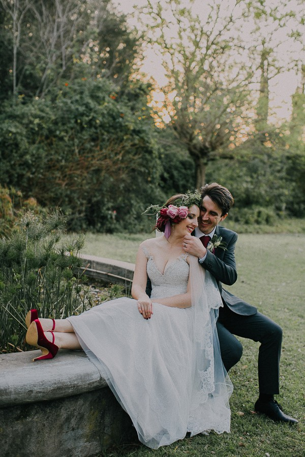 Bride and groom sitting on edge of fountain at Simondium Country Lodge