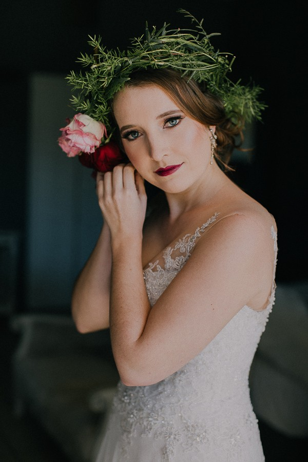 Bride with flower crown putting on earring