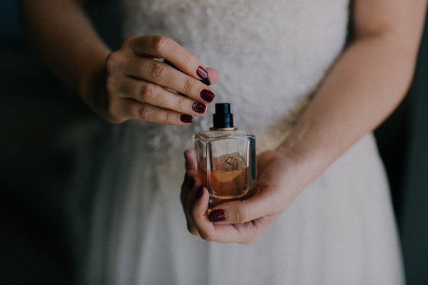 Bride holding bottle of perfume