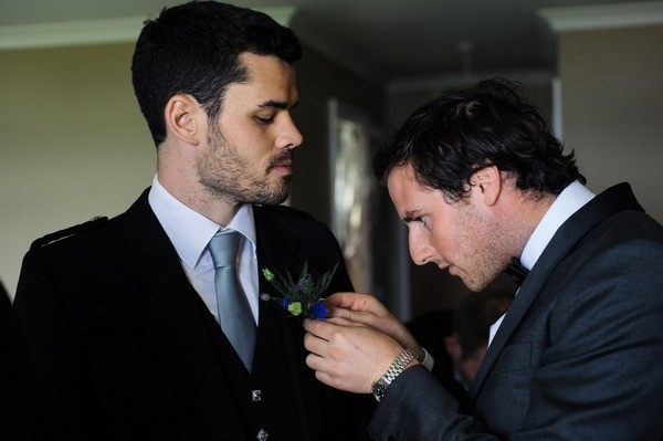Best Man Attaching Buttonhole to Groom's Suit Jacket