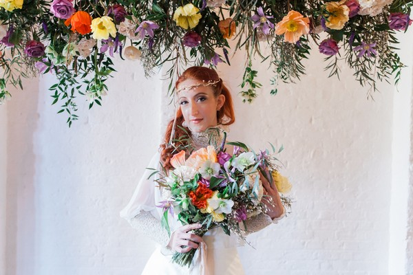 Bride holding colourful bouquet under hanging floral arrangement