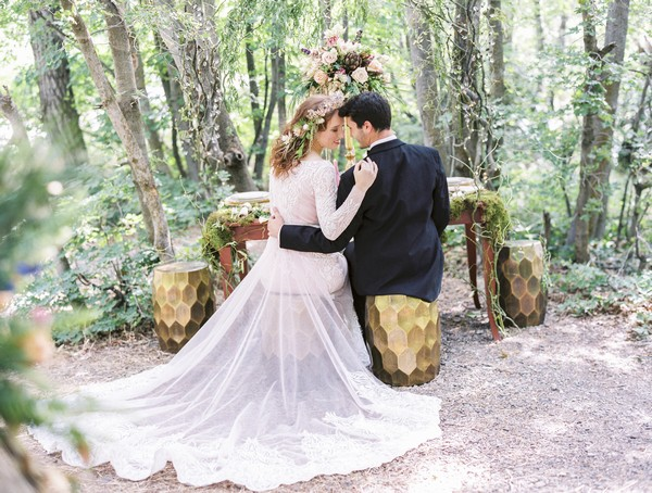 Bride and groom sitting at wedding table in woodland setting for A Midsummer Night's Dream wedding shoot