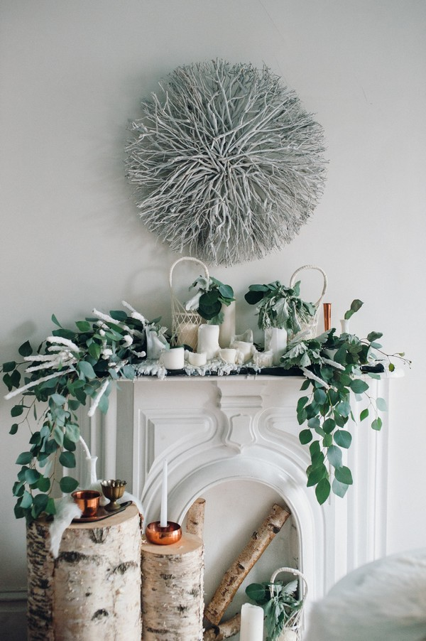 White mantelpiece decorated with foliage and candles