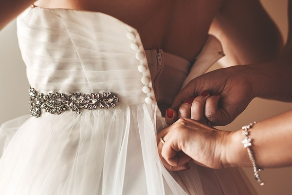 Fastening back of bride's wedding dress