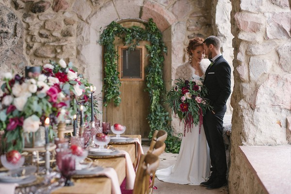Bride and groom next to wedding table