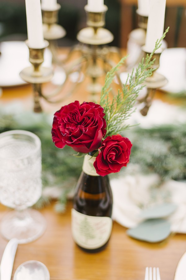 Red roses in bottle on wedding table