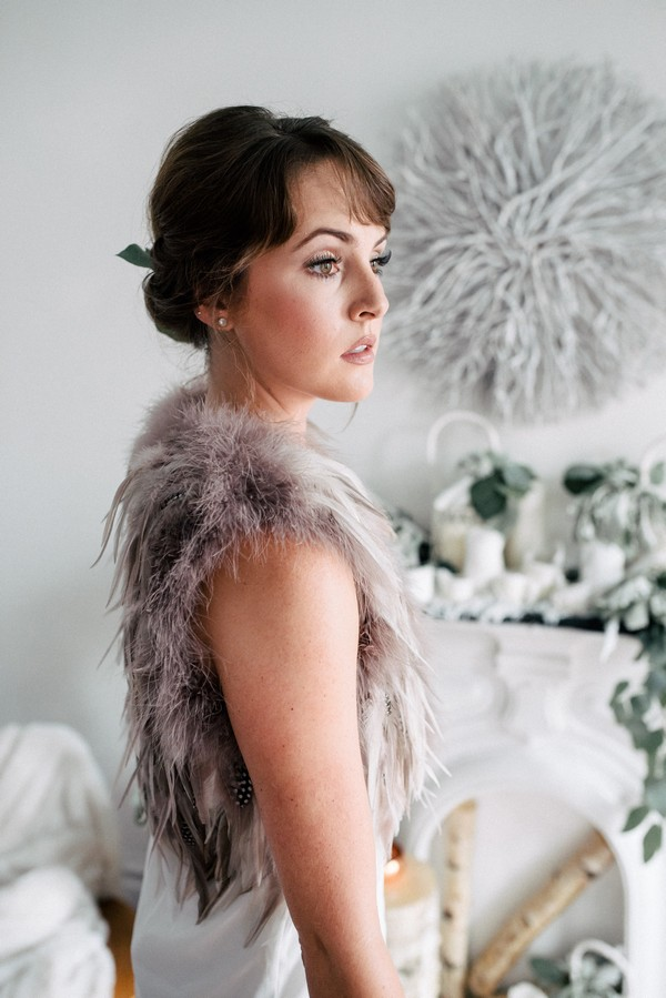 Bride with updo wearing fur and feather shrug