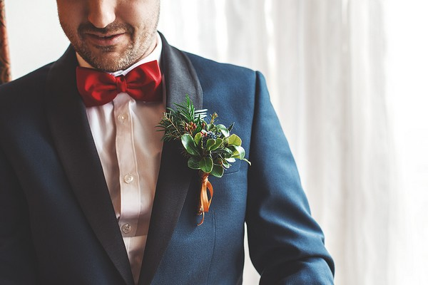Groom wearing red bow tie, blue jacket and Christmas buttonhole