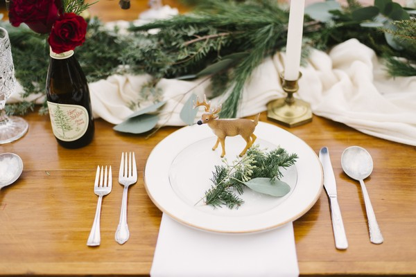 Deer and sprig of Christmas tree on plate at wedding place setting