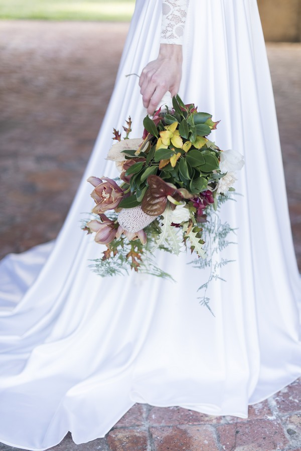 Bride holding winter wedding bouquet by her side