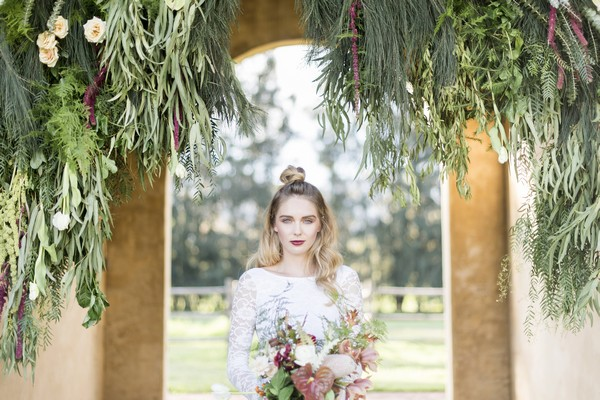 Bride standing under hanging foliage display