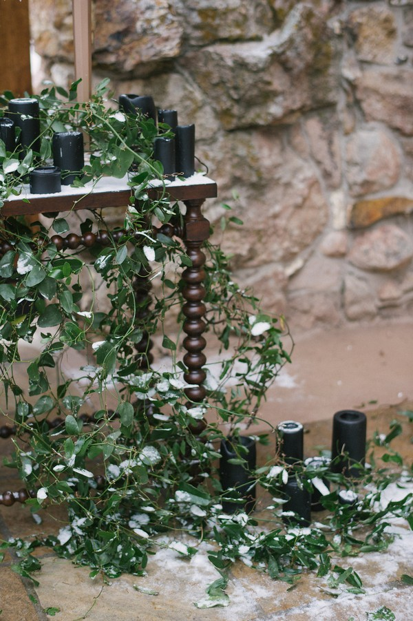 Foliage and black candles on wedding ceremony table