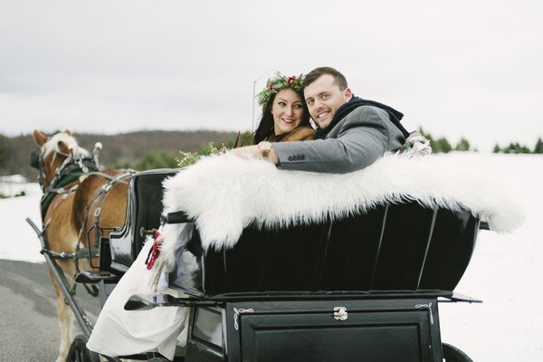 Bride and groom sitting in back of horse and cart carriage