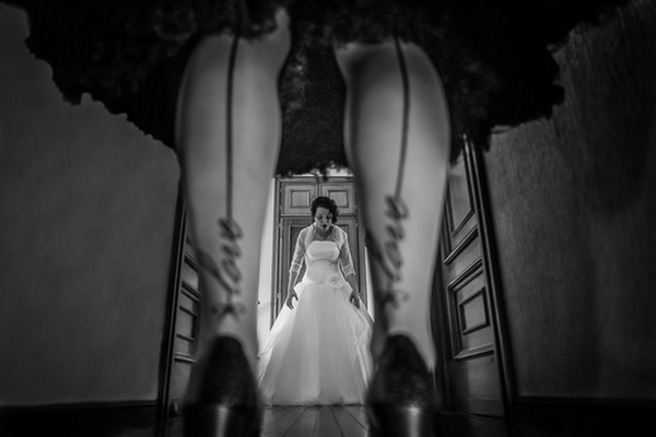 Picture of bride taken through legs of woman wearing tights with love written on seam - Picture by Alberto De La Fuente