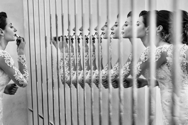 Ripple effect of bride's reflection in mirror as she puts on lipstick - Picture by Artan Media