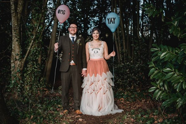 Bride and groom holding balloons in the woods - Picture by Esme Mai Photography