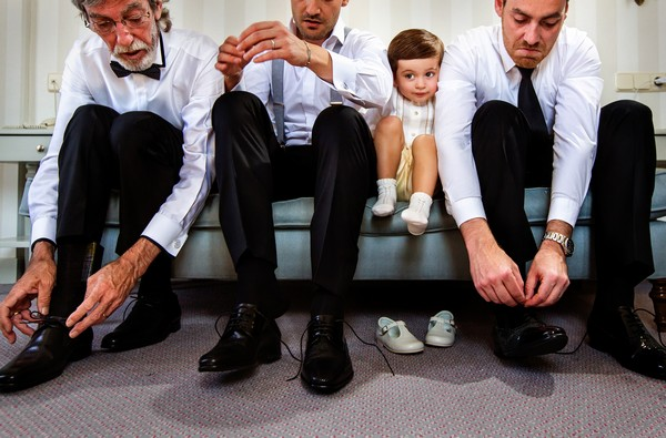 Pageboy being squashed between groomsmen tying their shoes - Picture by Virginia Gimeno