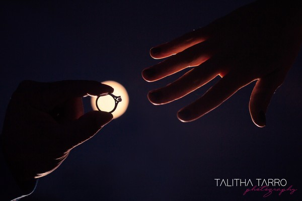 Moon shining behind wedding ring about to be put on finger - Picture by Talitha Tarro