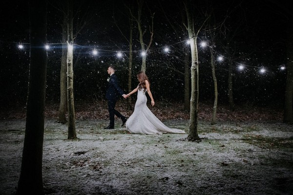 Bride and groom walking through trees in snow at night - Picture by Shoot It Momma