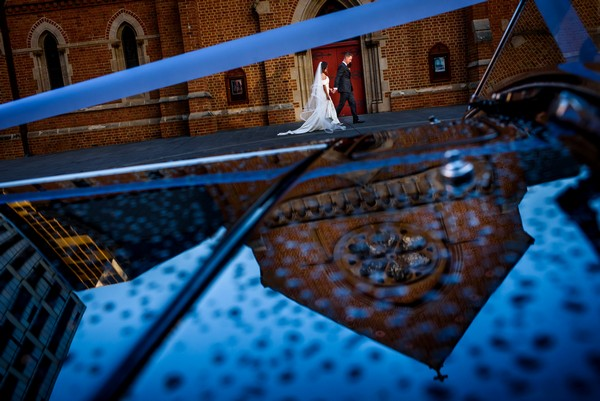 Reflection of church in wedding car as bride and groom walk past - Picture by Jason Tey Photography