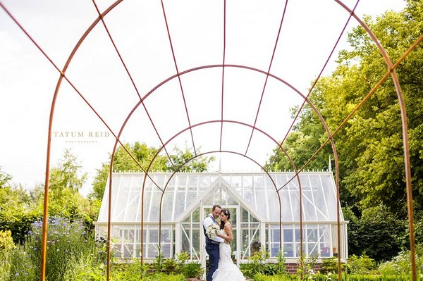 Bride and groom standing in front of large greenhouse - Picture by Tatum Reid Photography