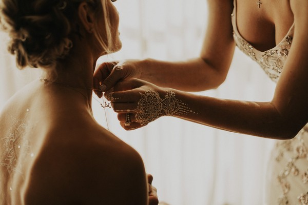 Woman with henna hand drawing helping bride put on necklace - Picture by India Earl Photography