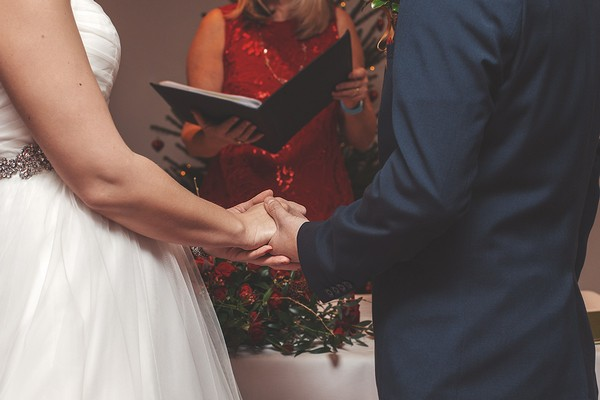 Bride and groom holding hands at the altar