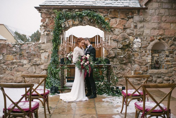 Bride and groom standing in front of wedding ceremony table
