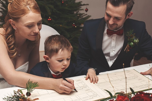 Bride signing register as pageboy watches