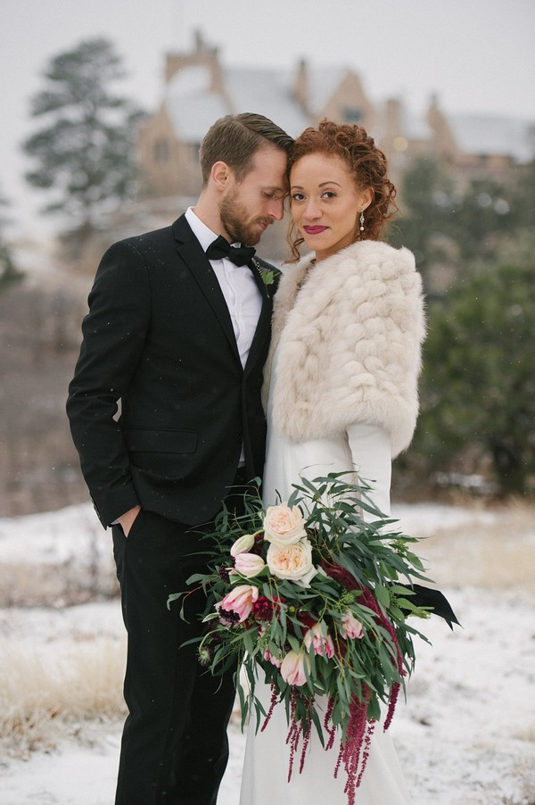 Bride holding winter wedding bouquet with groom