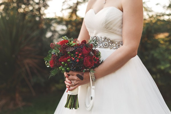 Bride holding red Christmas style bouquet