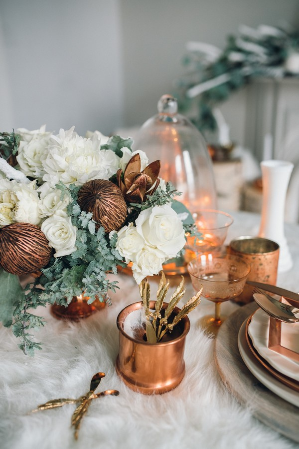 Copper cups and white flowers on wedding table
