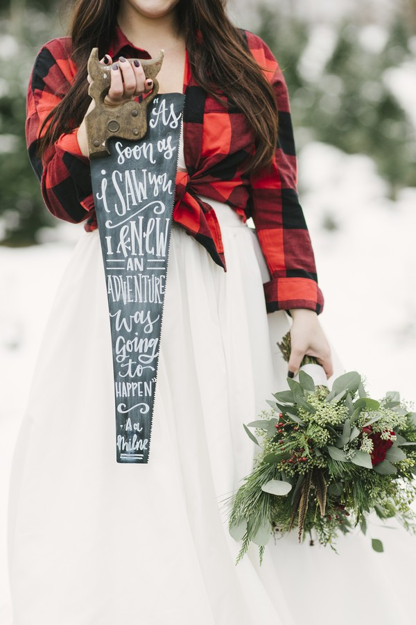 Bride holding saw with message written on it