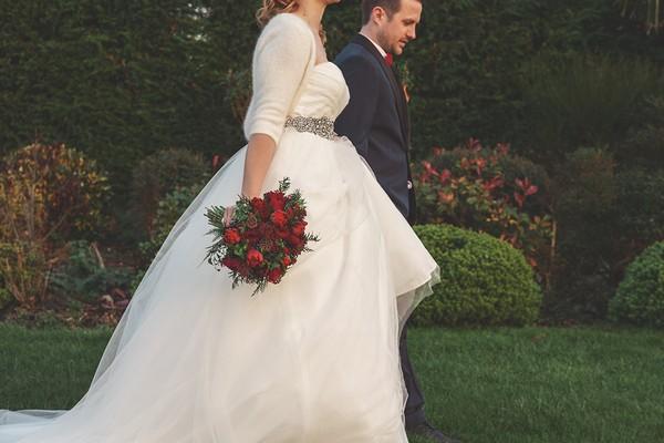 Bride walking holding bouquet by side