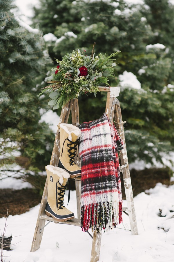 Winter boots, blanket and bouquet on ladder
