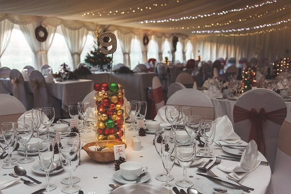 Glass jar of Christmas baubles on wedding table